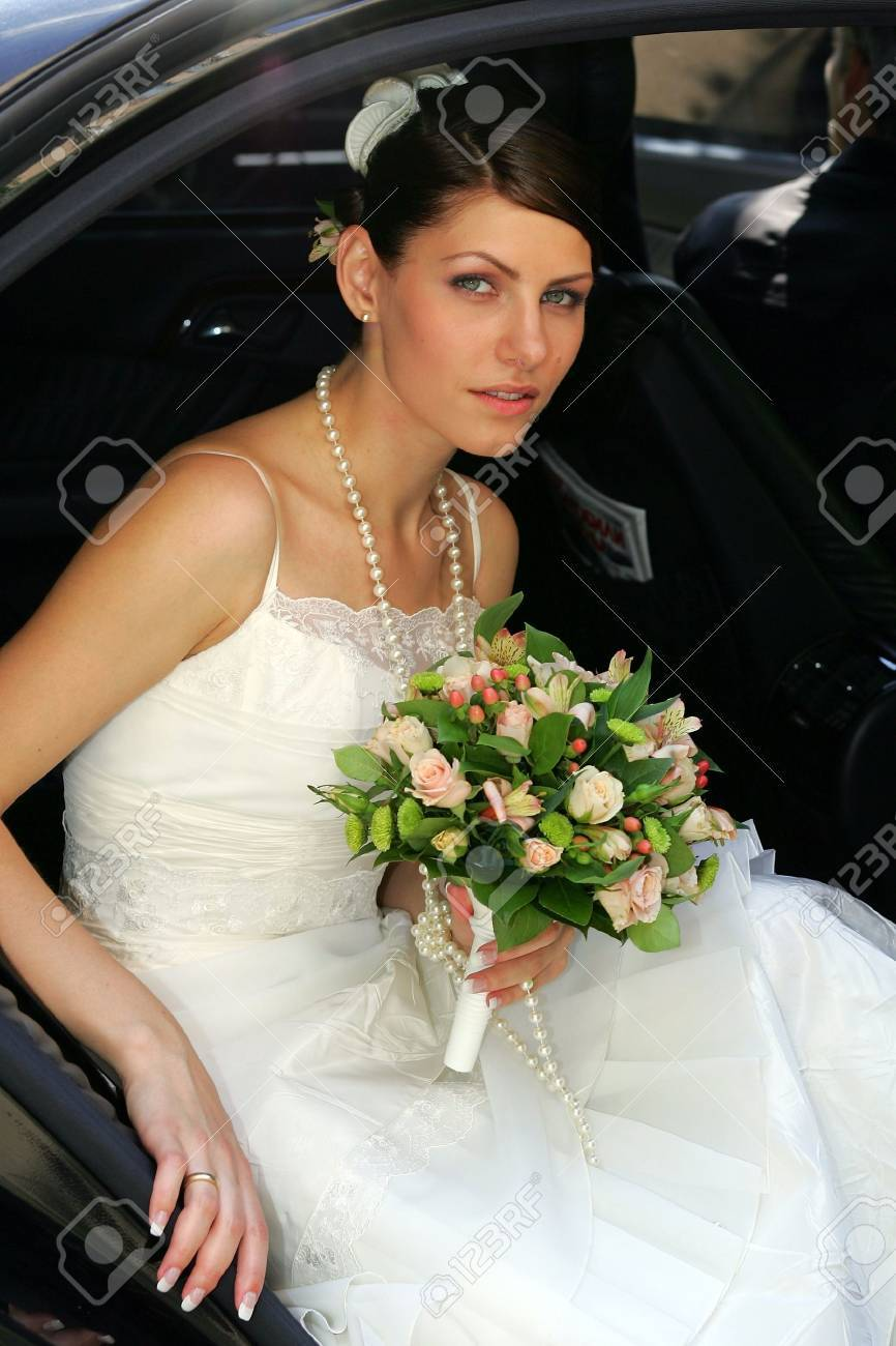 A bride getting out of her wedding car holding a bouqut of flowers Stock Photo - 1858550