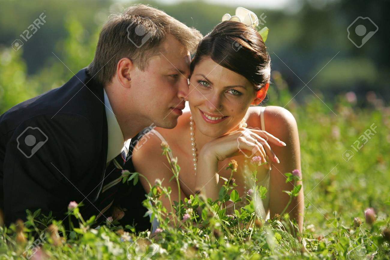 A portrait of a newly married man and woman embracing in a field Stock Photo - 2123874