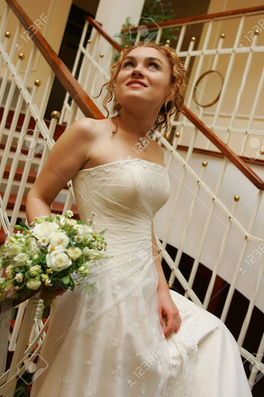 A bride walking down som stairs on her way to church with a bouquet of flowers. Stock Photo - 2142485