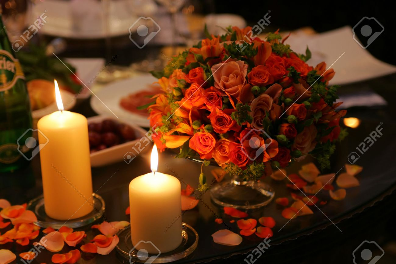 Two burning candles next to a bouquet of flowers on a table stock photo two burning candles next to a bouquet of flowers on a table scattered with petals izmirmasajfo Gallery