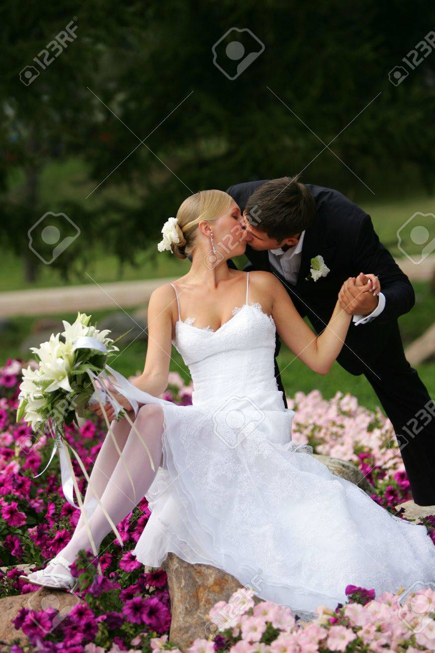 A portrait of a newly married man and woman. The bride and groom are kissing each other, and the bride is wearing a traditional white wedding dress and holding a bouquet of flowers in her hands. Stock Photo - 2471056