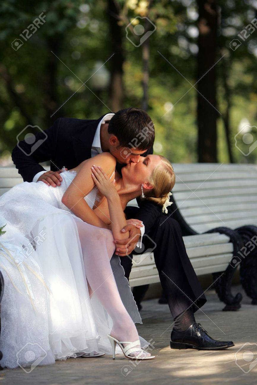 Newlywed couple in traditional wedding clothes kissing passionately on park bench. Stock Photo - 2495039