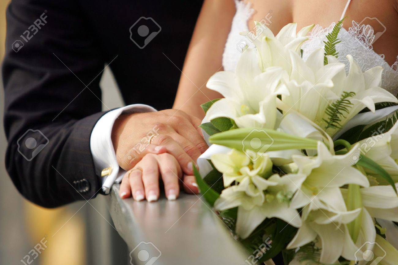 Bride and groom holding hands to show off their wedding rings Stock Photo - 2624773