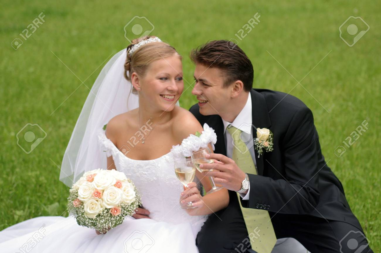 Happy newlywed couple sat in field on wedding day. Stock Photo - 3743202