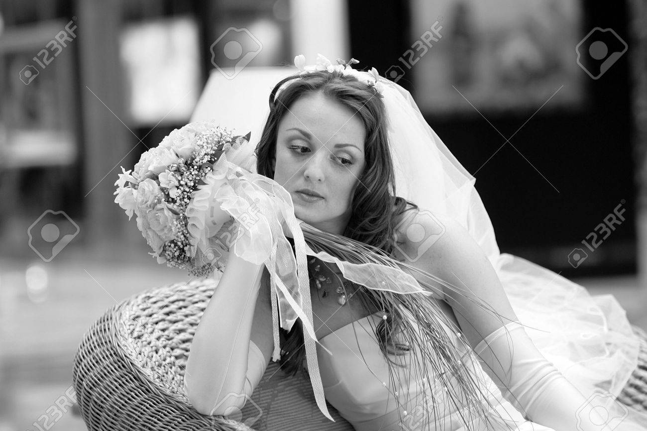 Fashionable young bride wearing white dress with veil holding bouquet, thoughtful expression. Stock Photo - 5111713