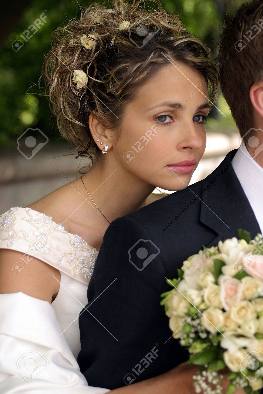 Pretty newlywed bride leaning on husbands shoulder with bouquet. Stock Photo - 5214983