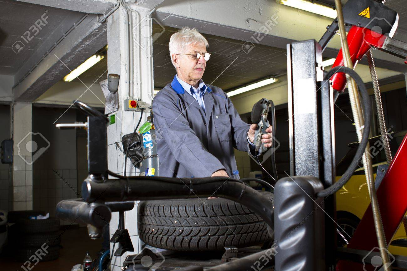 tire change technician in the repair shop stock photo picture and stock photo tire change technician in the repair shop