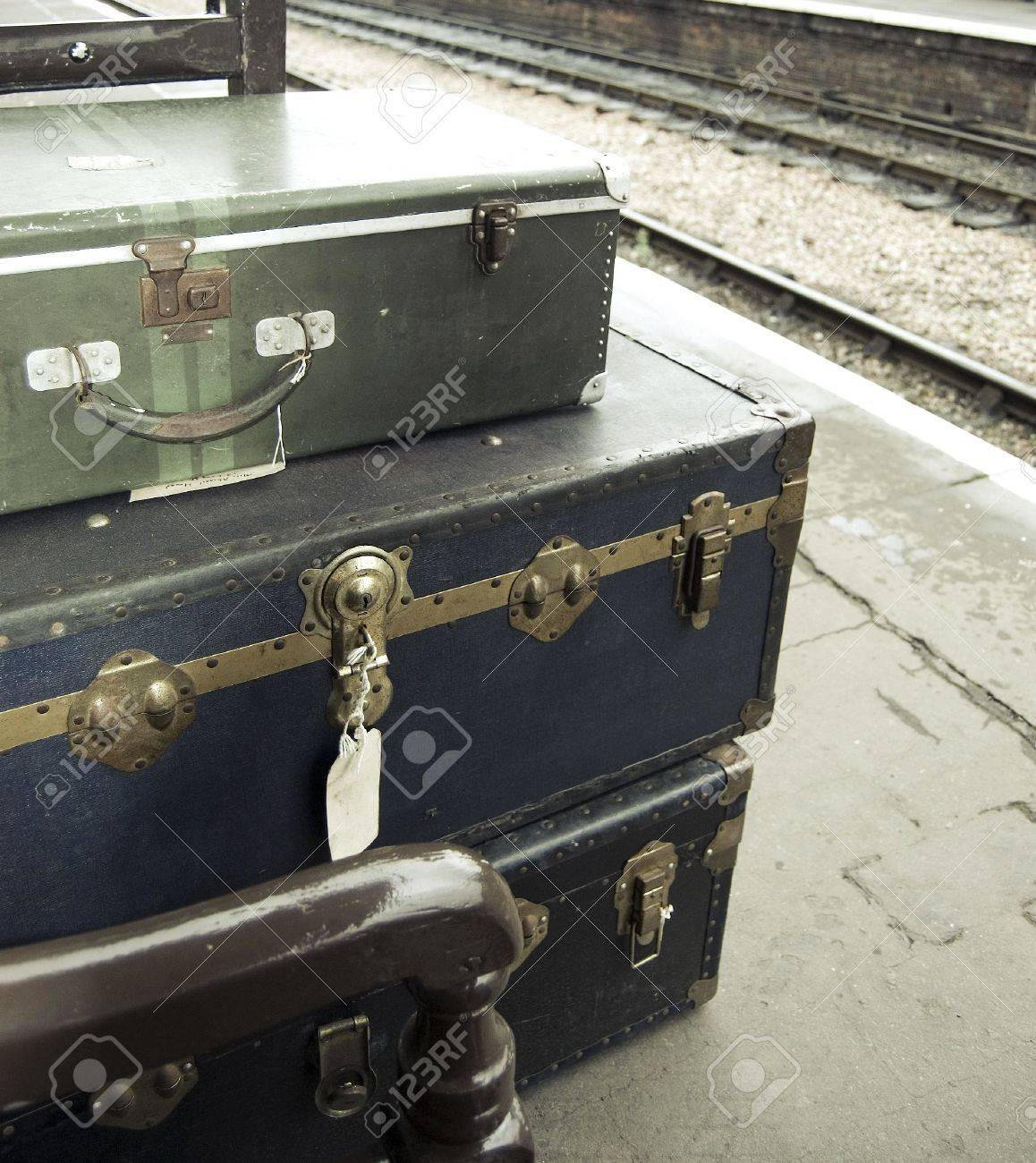 Old-fashioned personal baggage stacked up on train platform - 5743746