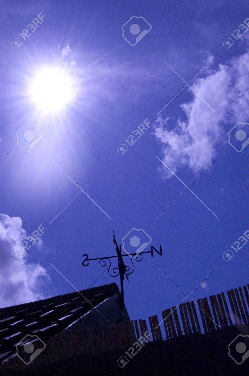 Silhouette of weather vane against blue sky - 5743747