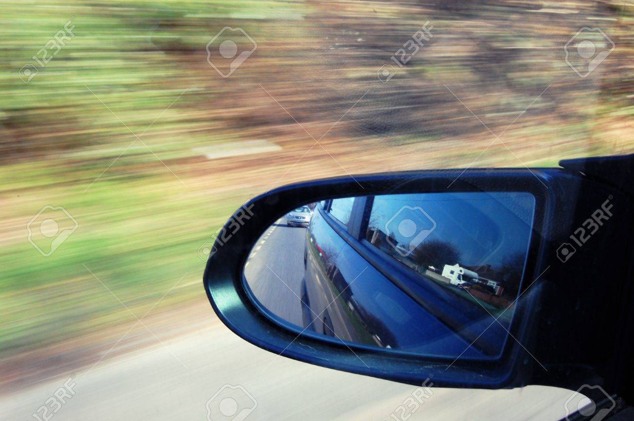 Wing mirror of car at high speed, view of traffic behind - 5743725