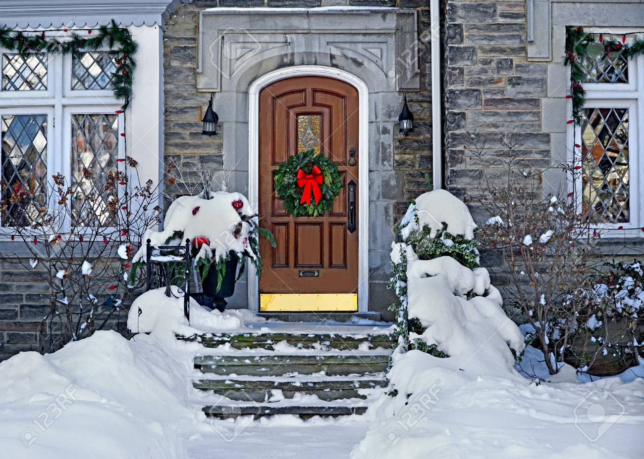 White Front Door With Christmas Wreath On A Snowy Day Stock Photo
