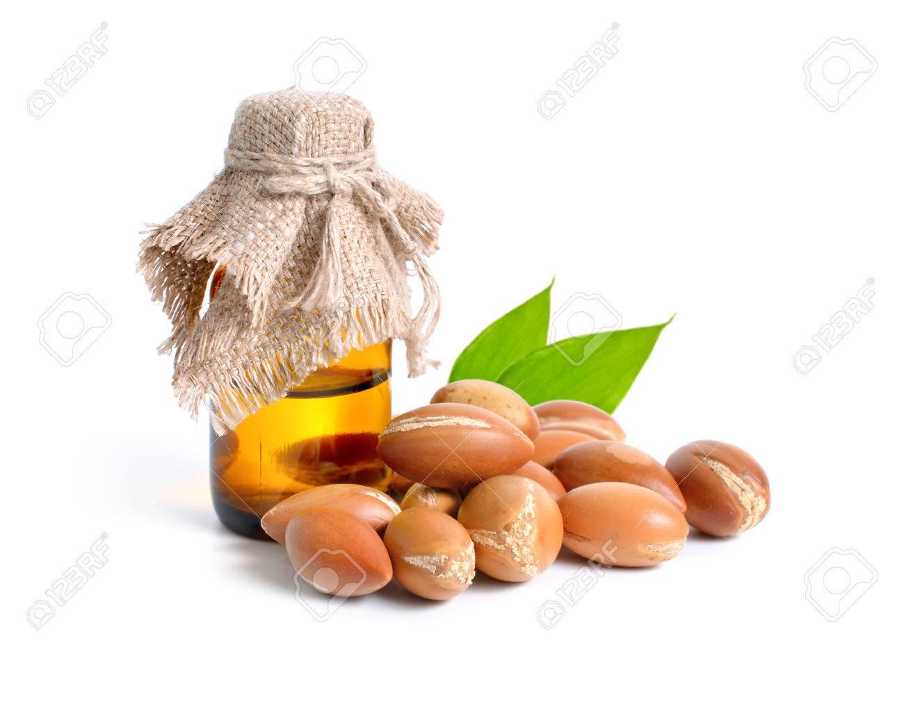 Argan seed with pharmaceutical bottle. Isolated on white background. - 77209739