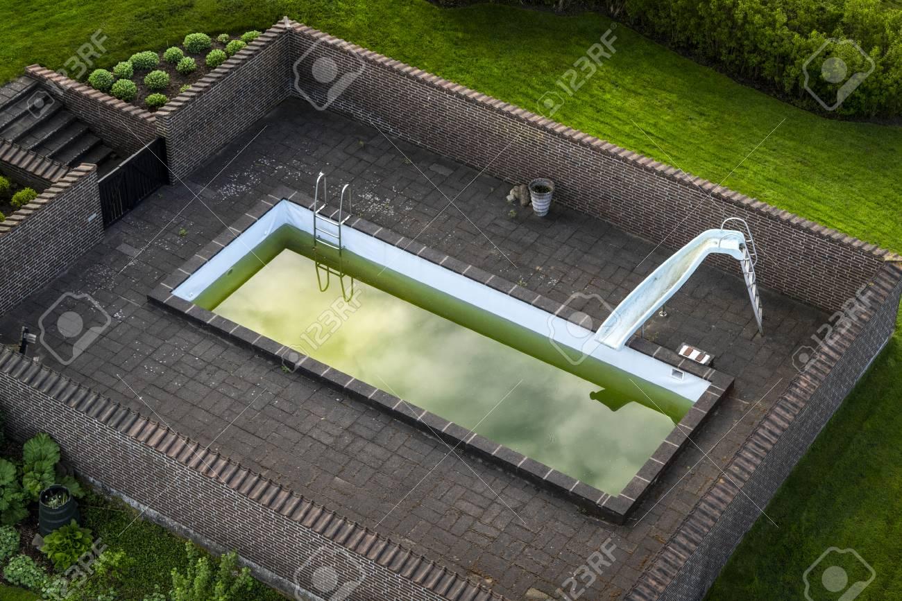 Terraza Con Una Piscina Con Agua Verde Rodeada Por Una Pared De