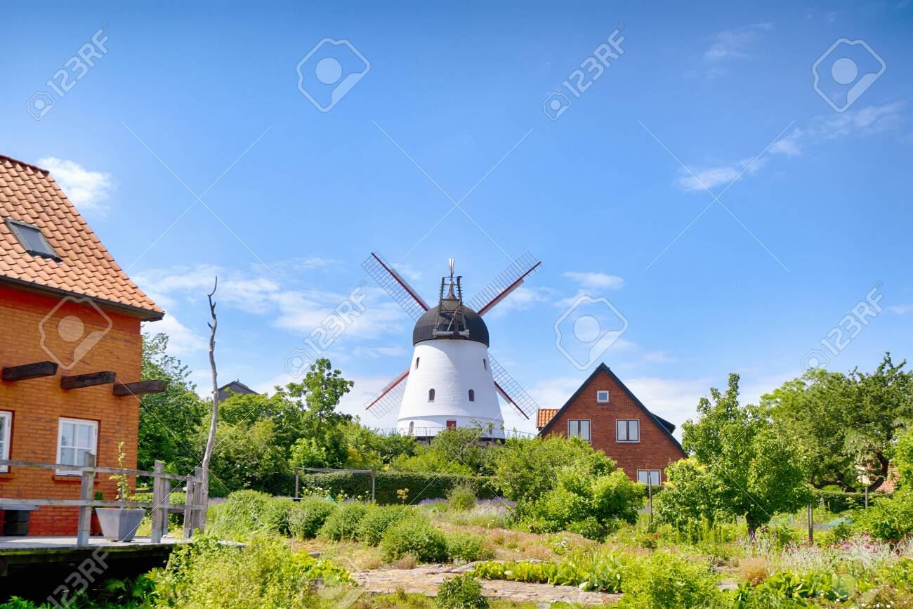 Old mill in a green garden in the summertime under a blue sky - 129713889