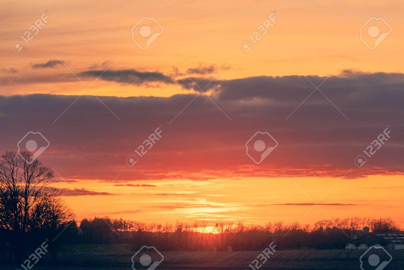 Countryside sunset with a beautiful horizon and dramatic clouds over farmland - 144427482