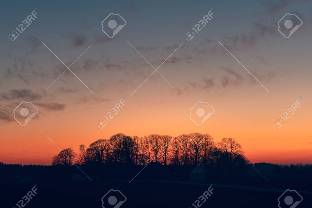 Sunset over a farmland with tree silhouettes ju8st before the sun is set - 144427484