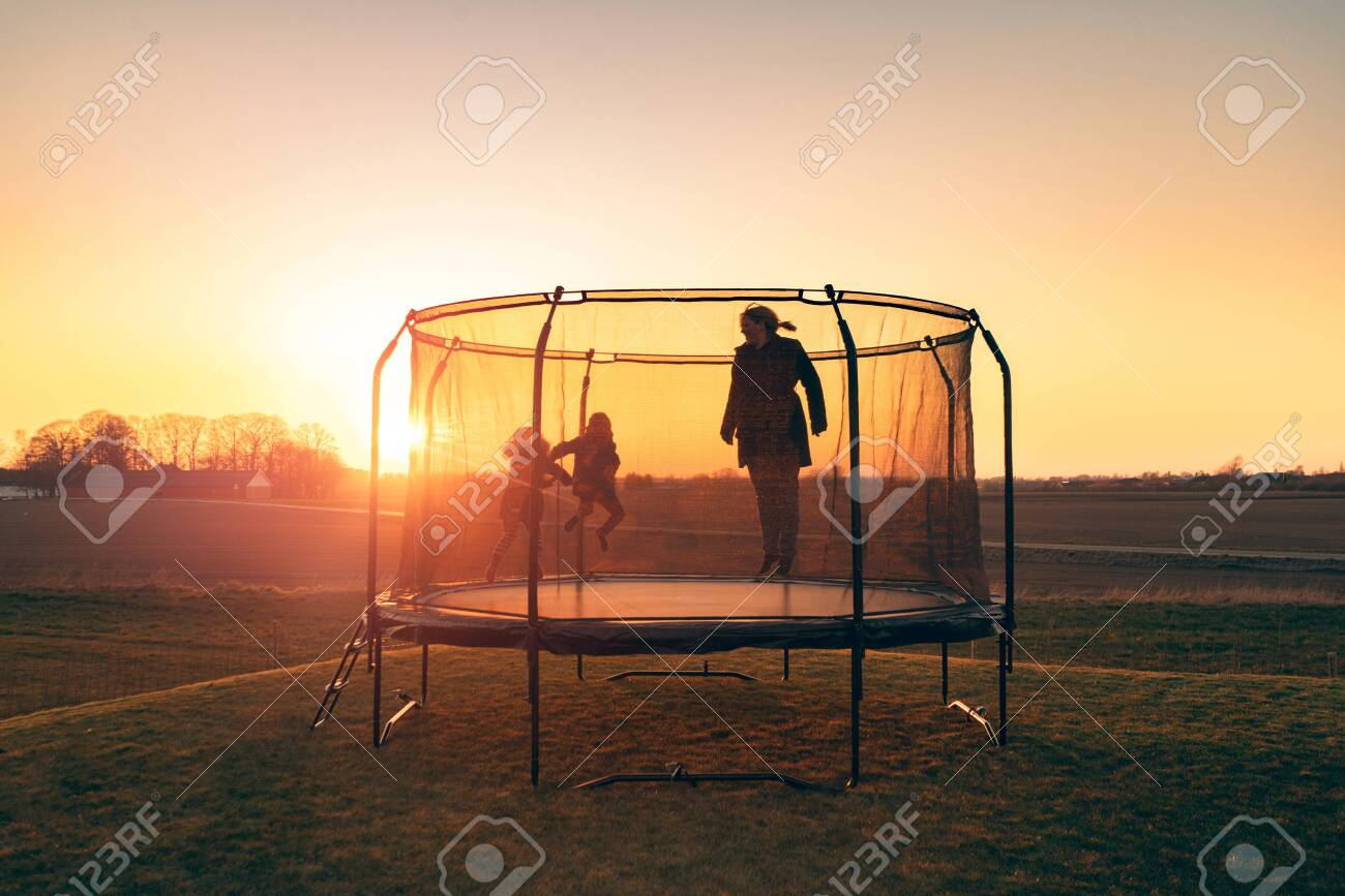 Trampoline on a lawn in the sunset with two kids and a young woman jumping and playing - 144427485