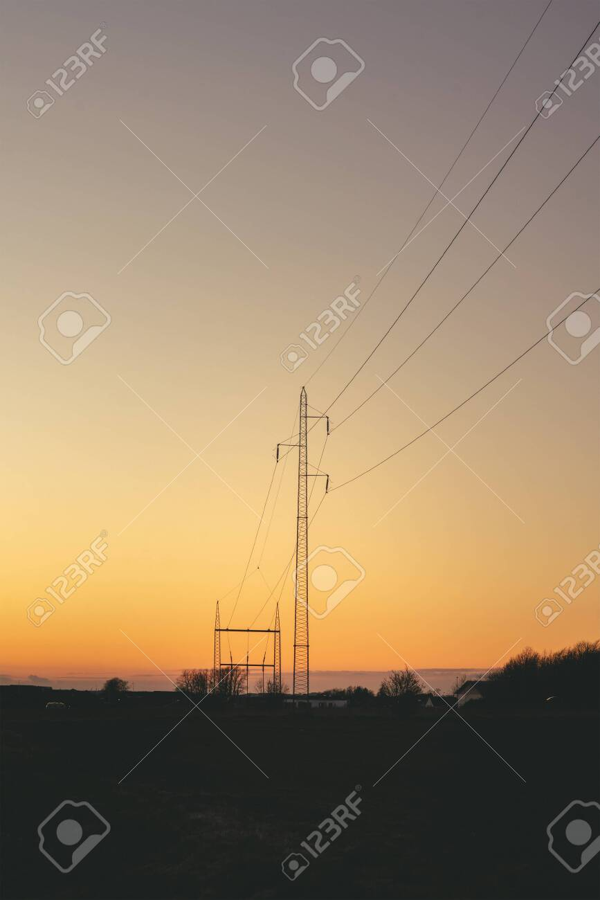 Electrical pylons at dawn in a beautiful sunset with a clear sky - 143854772