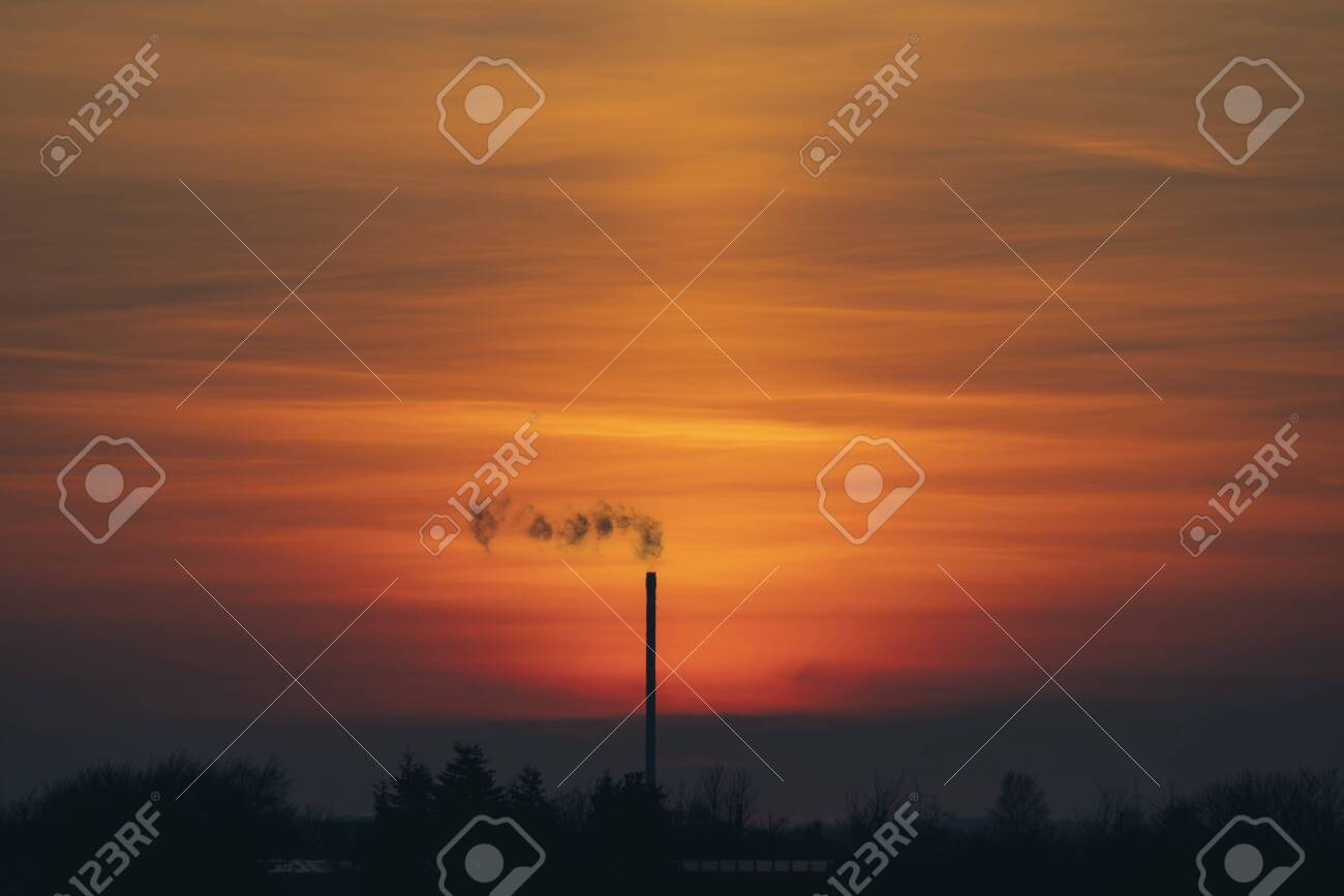 Smoke from a chimey in a beautiful sunset with industrial silhouettes - 145302151