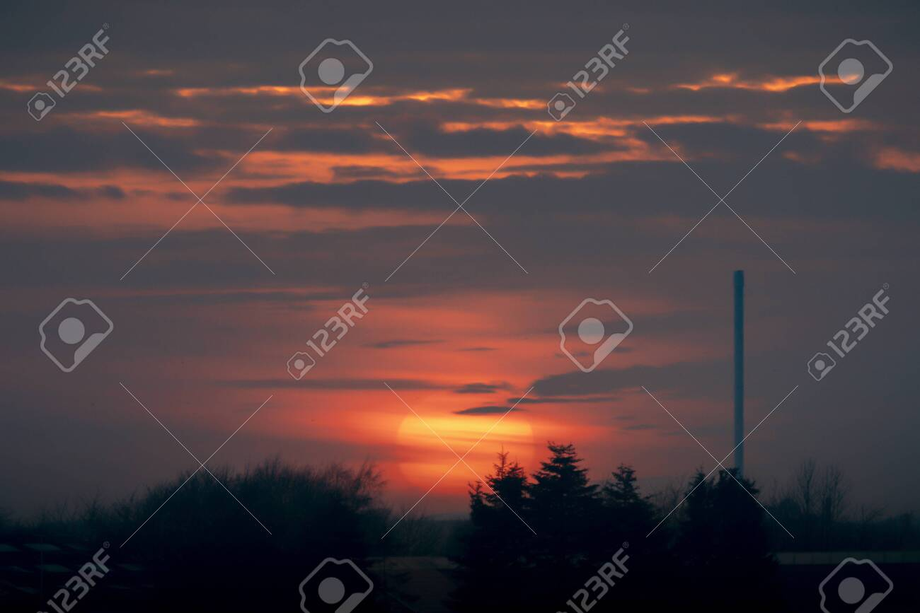 Beautiful sunset over an industrial facility at dawn with trees in front and a large chimney - 145302152
