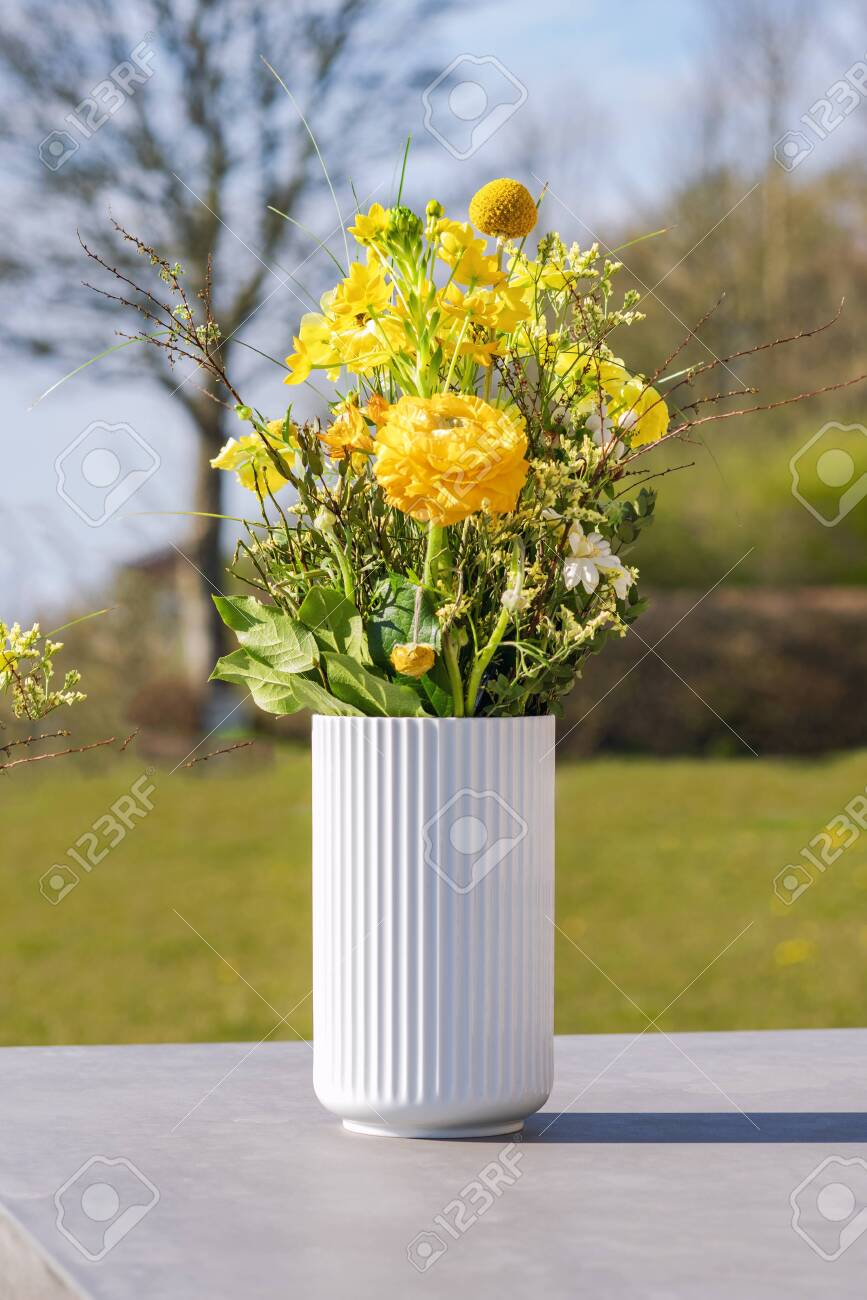 White vase with yellow wildflowers on a table on a countryside terrace - 146232602