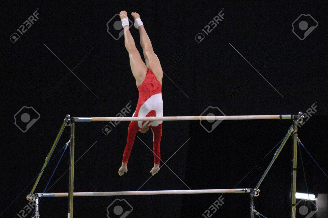 43d4f7530f9c A female gymnast preforms a routine on the uneven bars during competition.  Stock Photo -