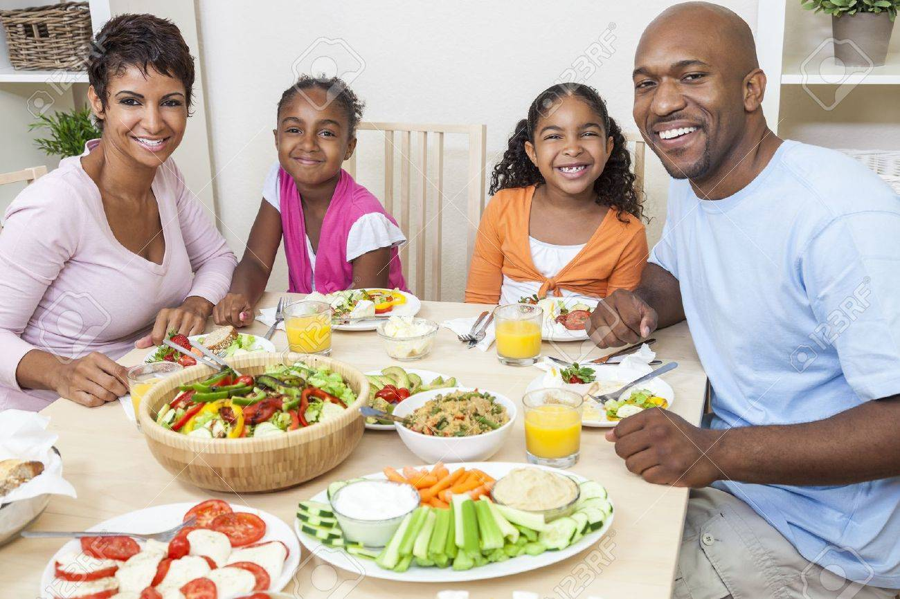 An attractive happy African American, smiling family of mother, father, two daughters eating salad and healthy food at a dining table. Stock Photo - 19407100