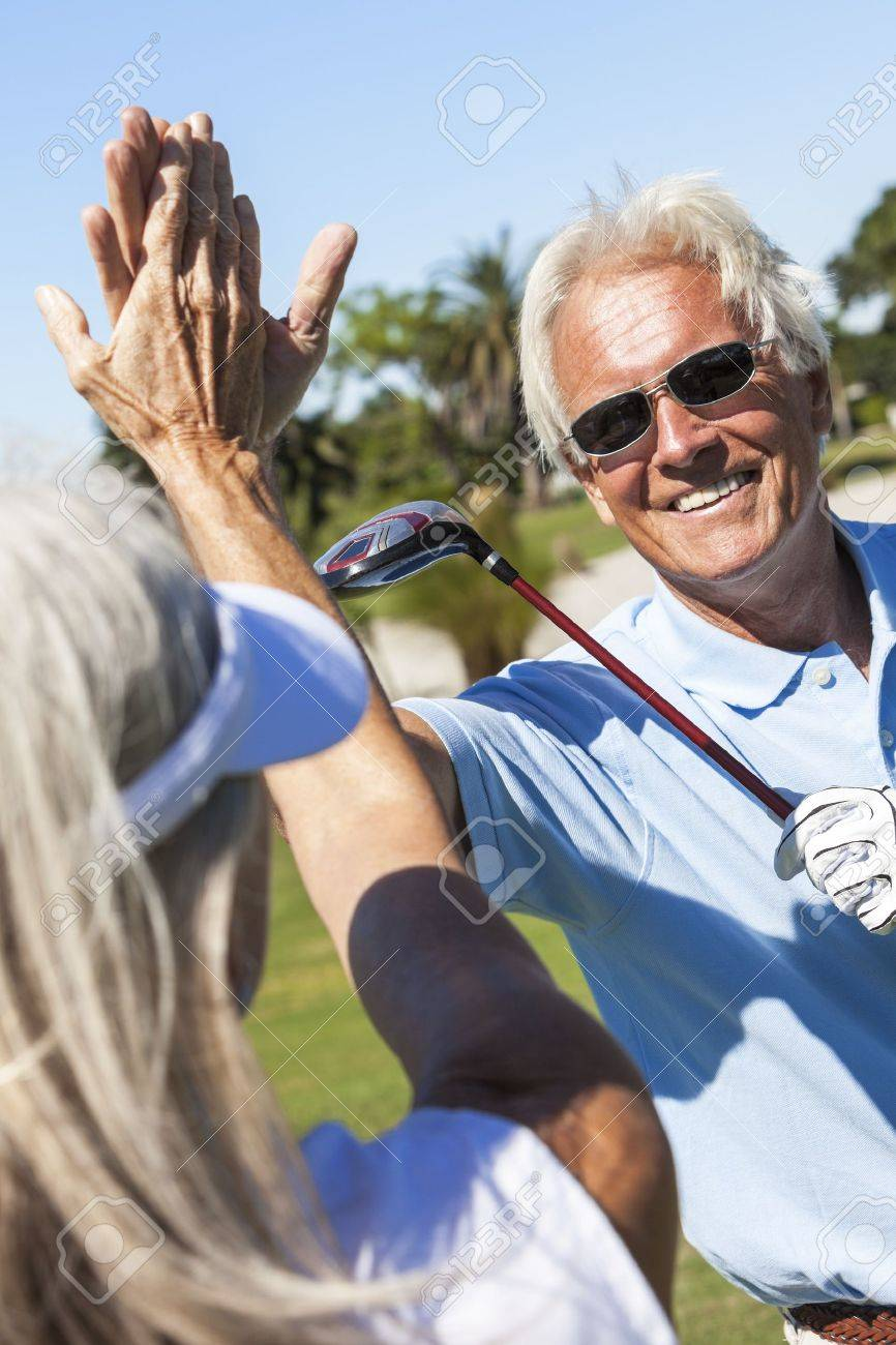 Happy senior man and woman couple together playing golf and celebrating a good shot on the course Stock Photo - 19407115