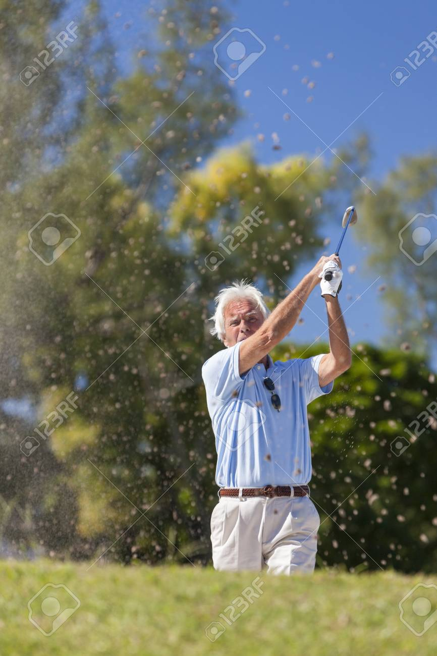 Happy senior man playing golf ball out of a sand trap or bunker on a golf course Stock Photo - 19407126