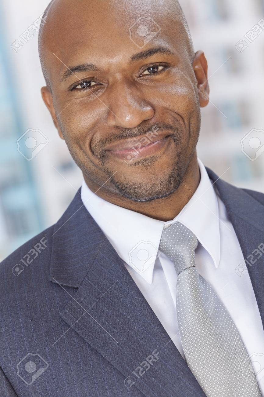 Happy smiling successful African American businessman or man in a suit in a modern city Stock Photo - 19407155