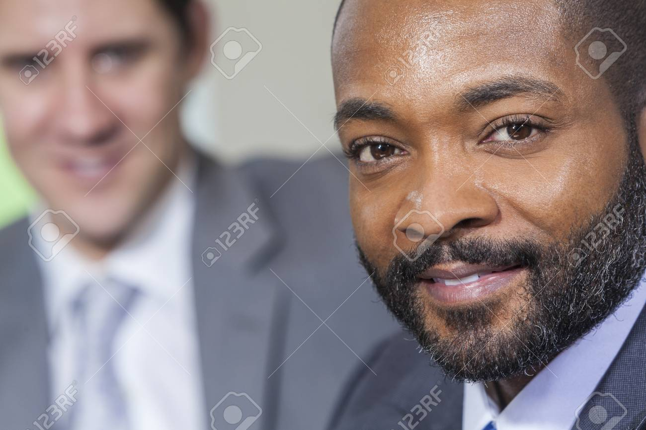 Successful African American businessman or man with his caucasian colleague behind him. Stock Photo - 19483560