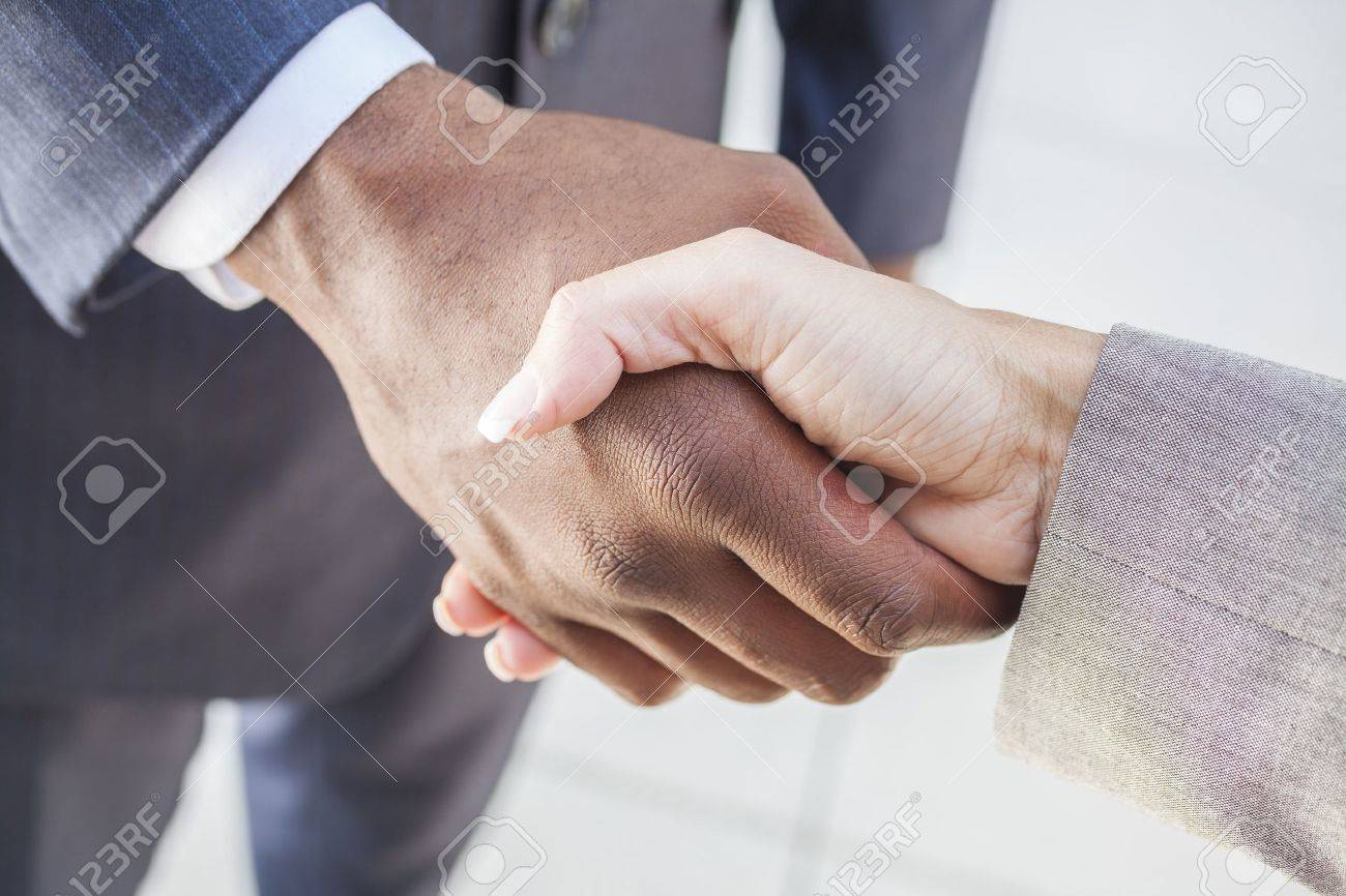 African American businessman or man shaking hands with a businesswoman or woman caucasian female colleague making a business deal Stock Photo - 19483555