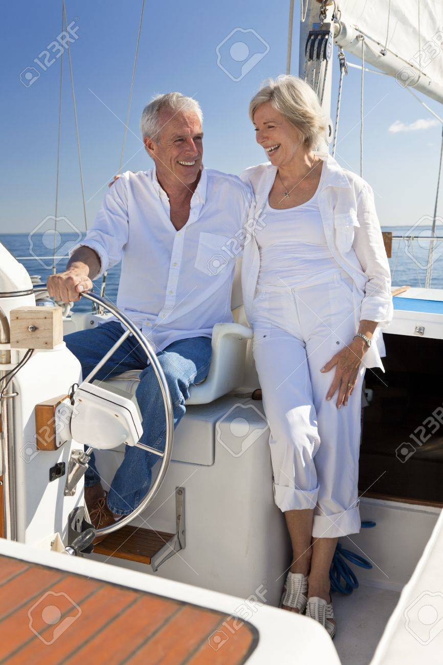 A happy senior couple sitting at the wheel of a sail boat on a calm blue sea Stock Photo - 19524115