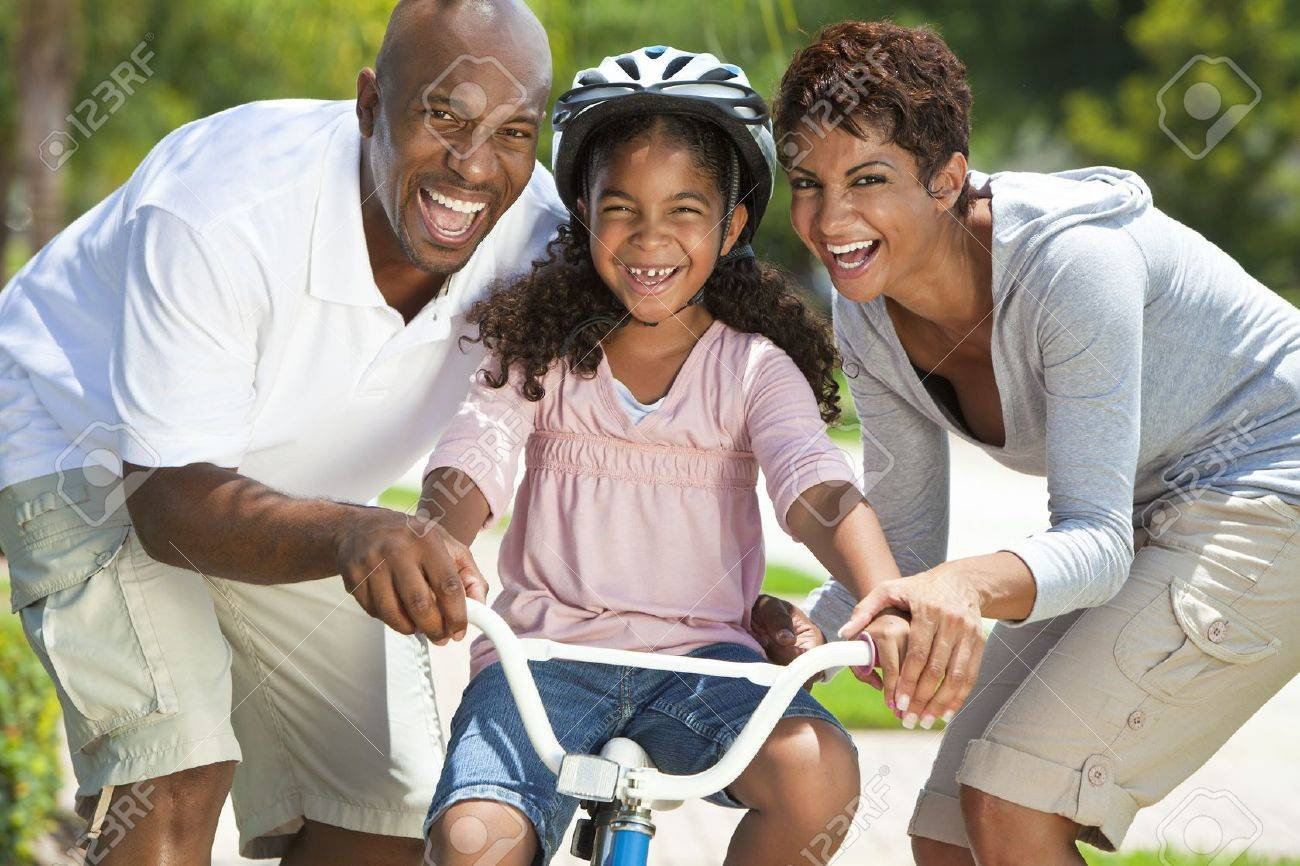 A young African American family with girl child riding her bicycle and her happy excited parents giving encouragement beside her Stock Photo - 19608549
