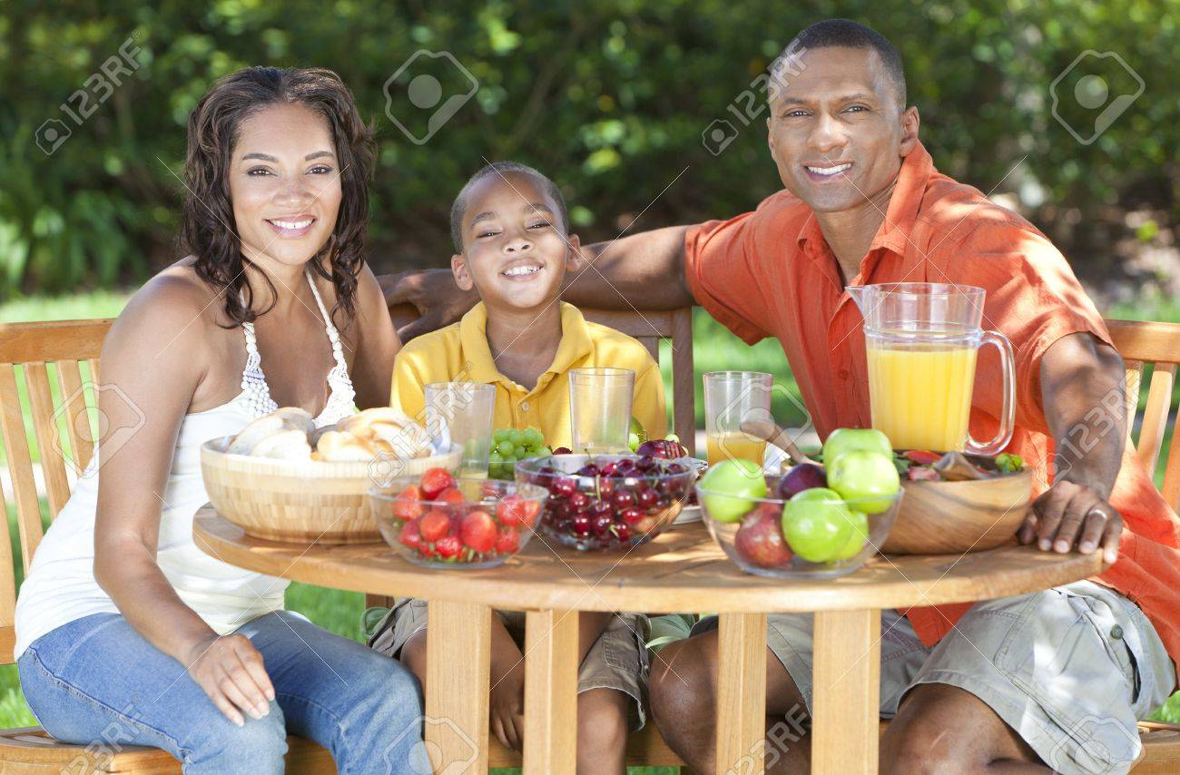 An attractive happy, smiling African American family of mother, father, son, man woman, boy child eating healthy food at a picnic table outside Stock Photo - 22037018