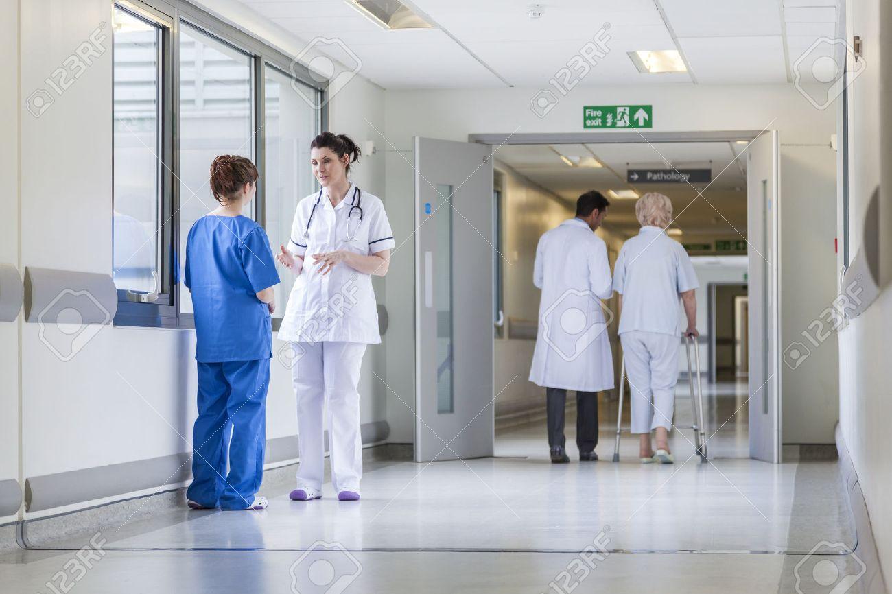 Hospital corridor with doctors, nurses & senior female patient Stock Photo - 22404349