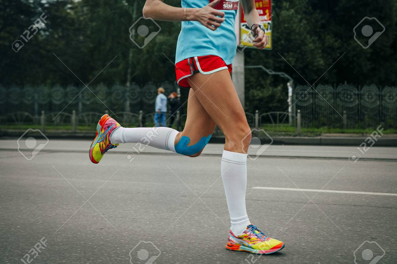 Girl running marathon, knees in blue kinesiology taping - 46426652