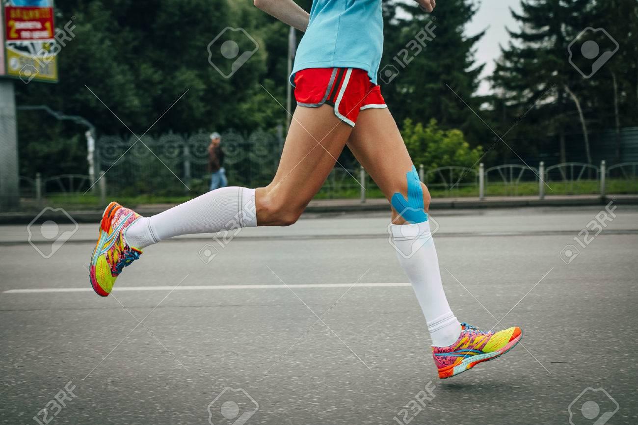 girl athlete running a marathon, knees in blue kinesiology taping - 46426656