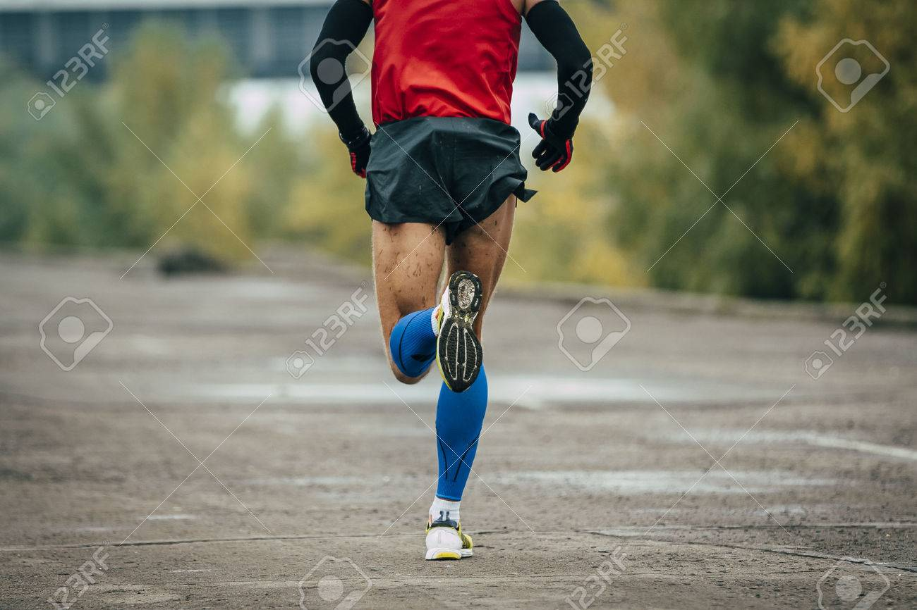 young man runs through streets. while running it on compression stockings and arm warmer - 46426665