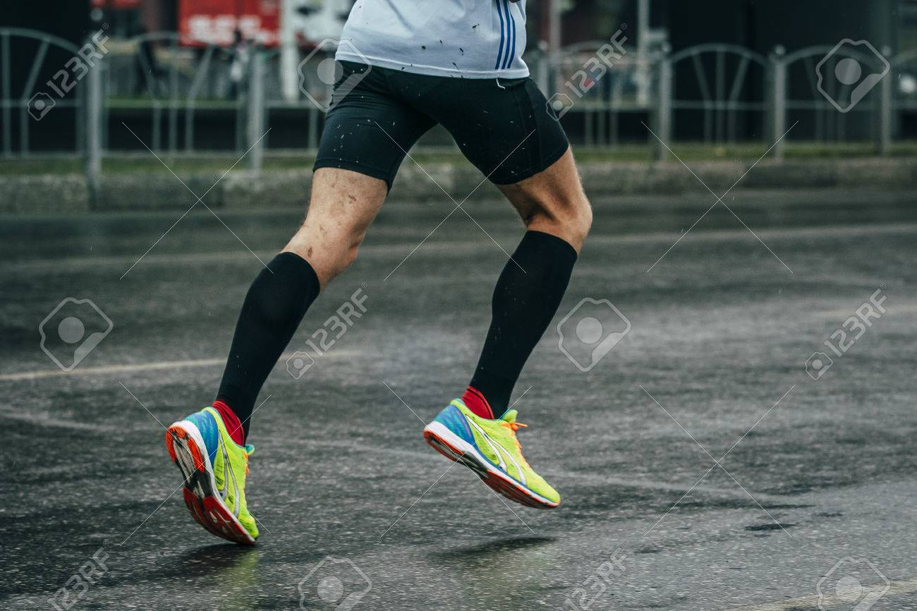 young man athlete runs a marathon on a wet road, rain drips - 46552744