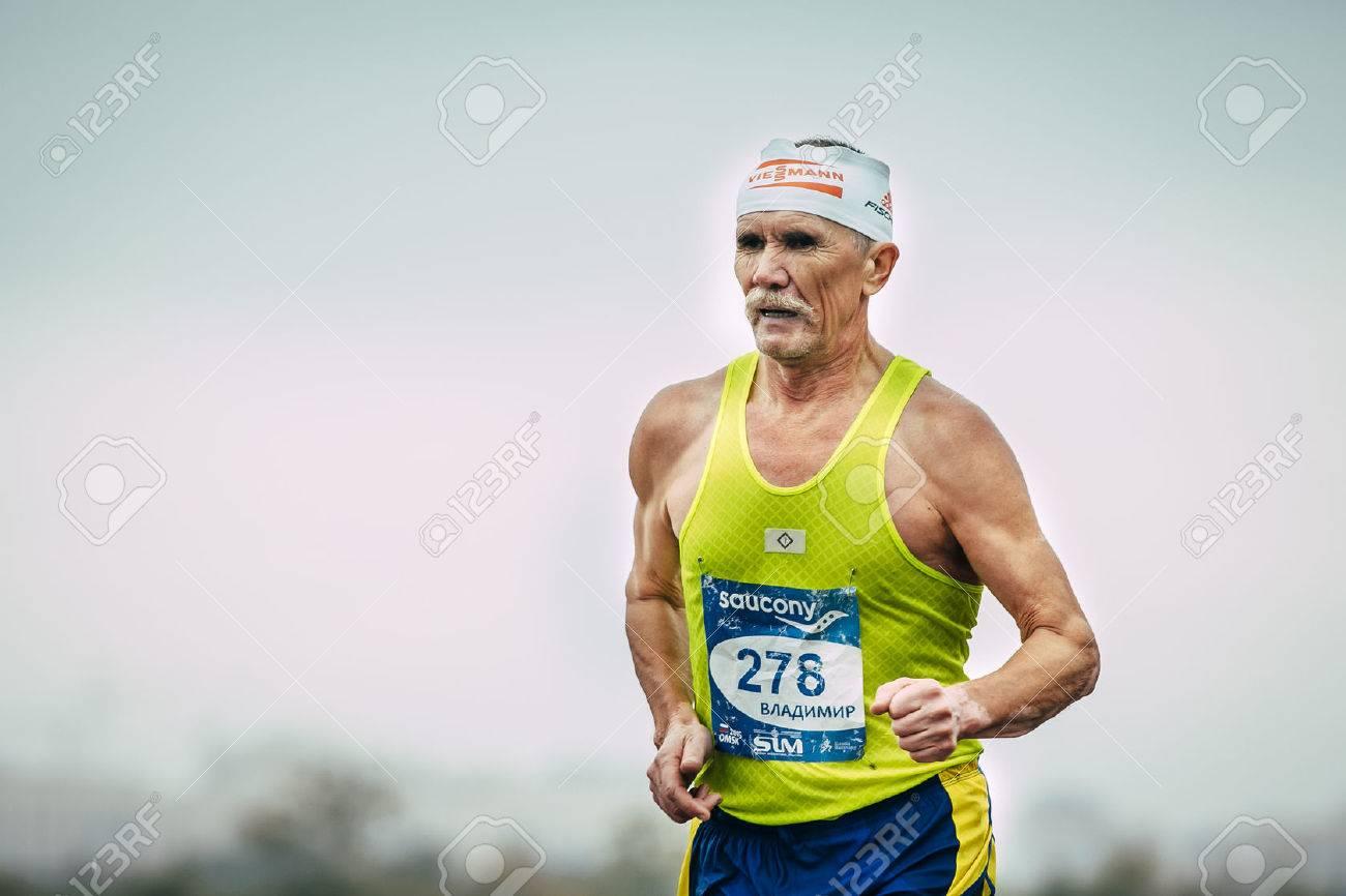 Omsk, Russia - September 20, 2015: elderly male runner running during Siberian international marathon. background of sky - 45849527