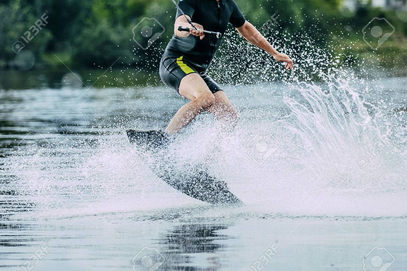 man jumps on wakeboard wave. summer lake - 49933766