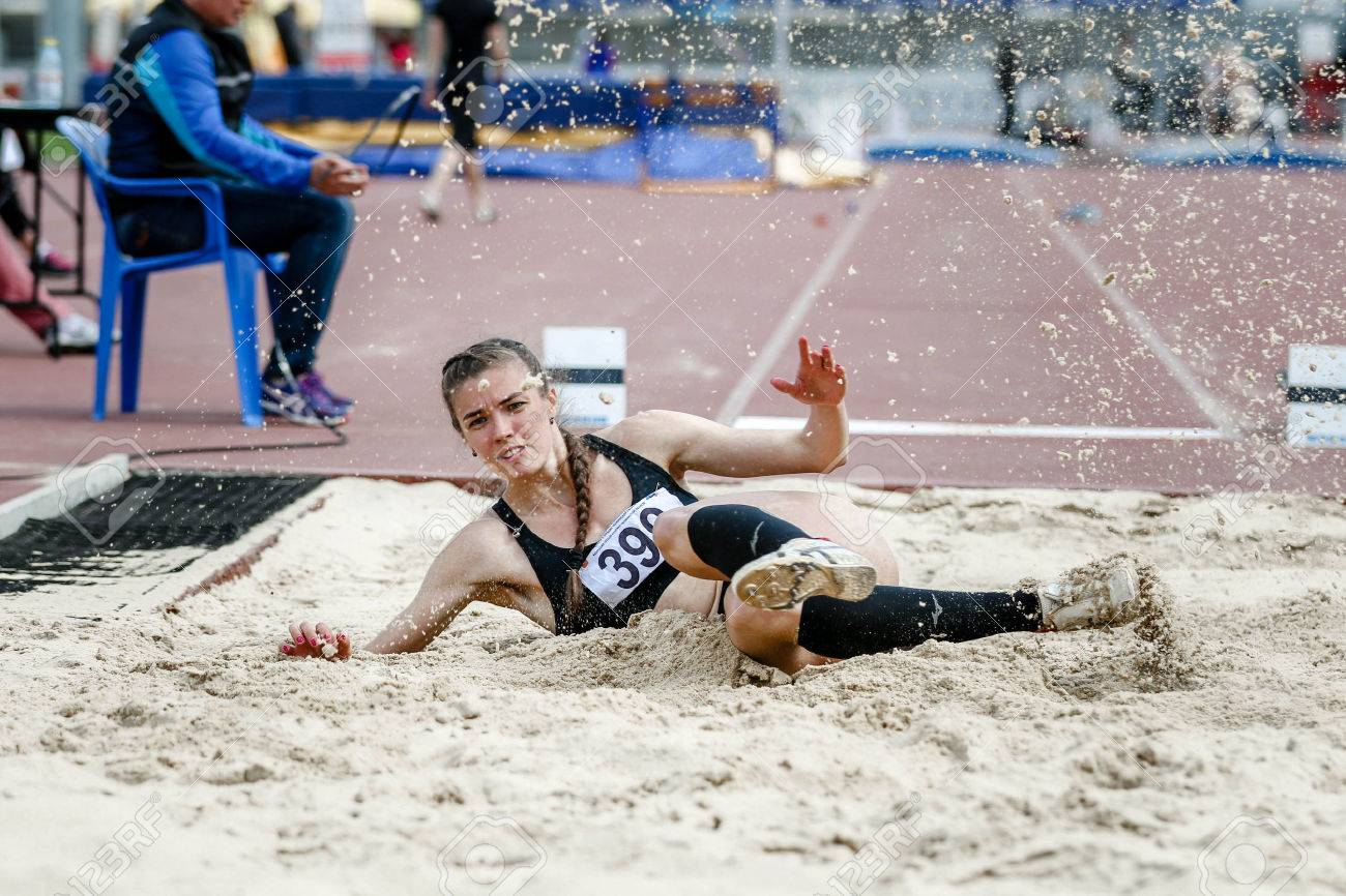 beautiful young woman athlete at competitions long jump. splashes of white sand upon landing. successful attempt - 50132572
