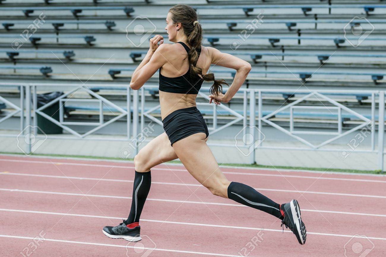 young woman athlete running sprint track stadium in summer. beautiful and slim body. compression socks feet - 50132578