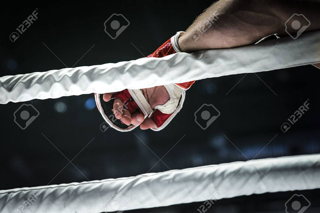 closeup hand of fighter MMA in glove lays ropes of ring - 50211365