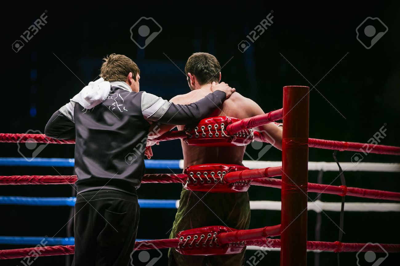 mixed martial arts fighter (MMA) stands in corner ring next to him coach. break between rounds in fight - 50415150
