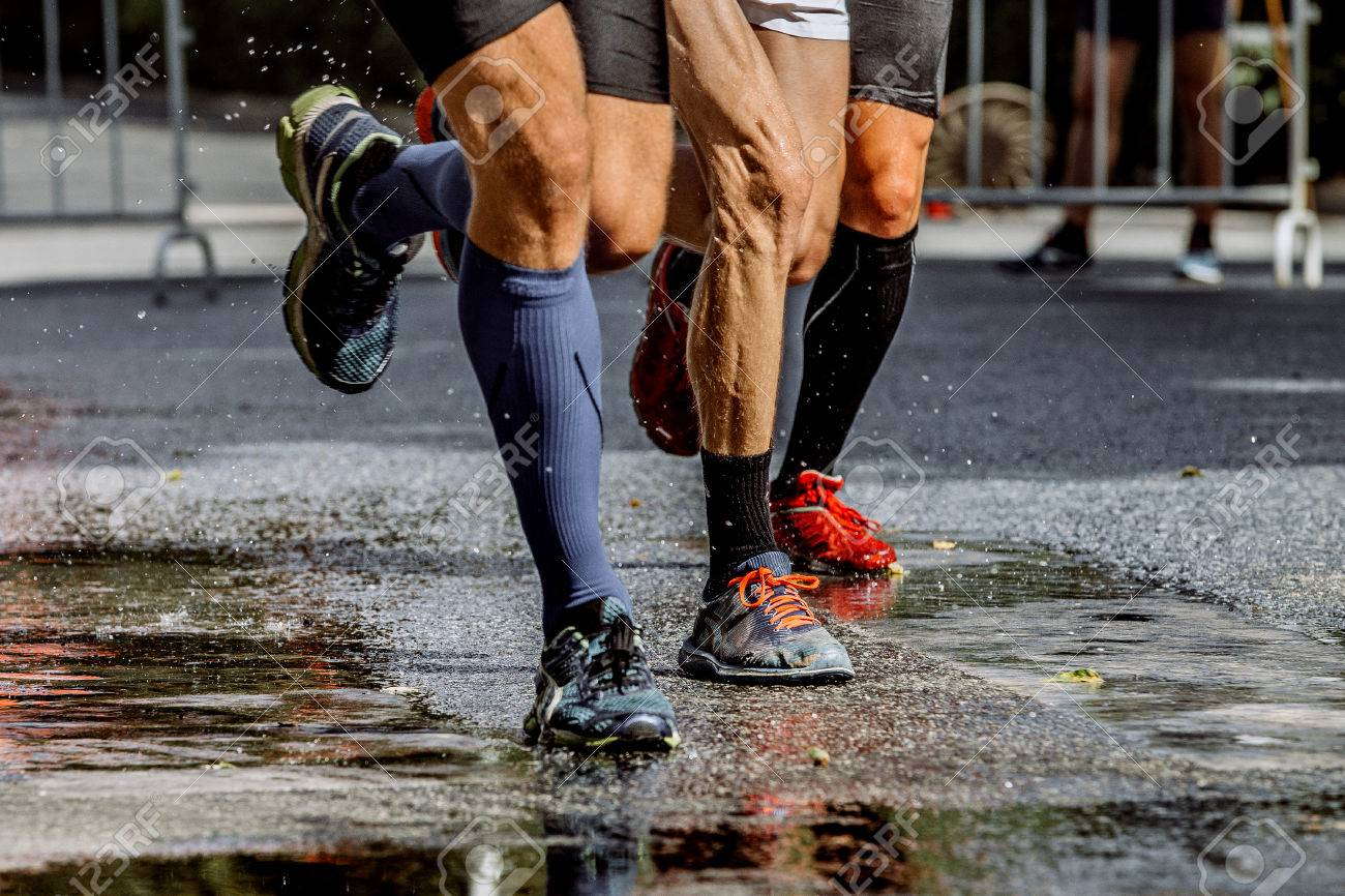 Legs Of Three Male Marathon Runners Water Splashes From Under Running Shoes Stock Photo