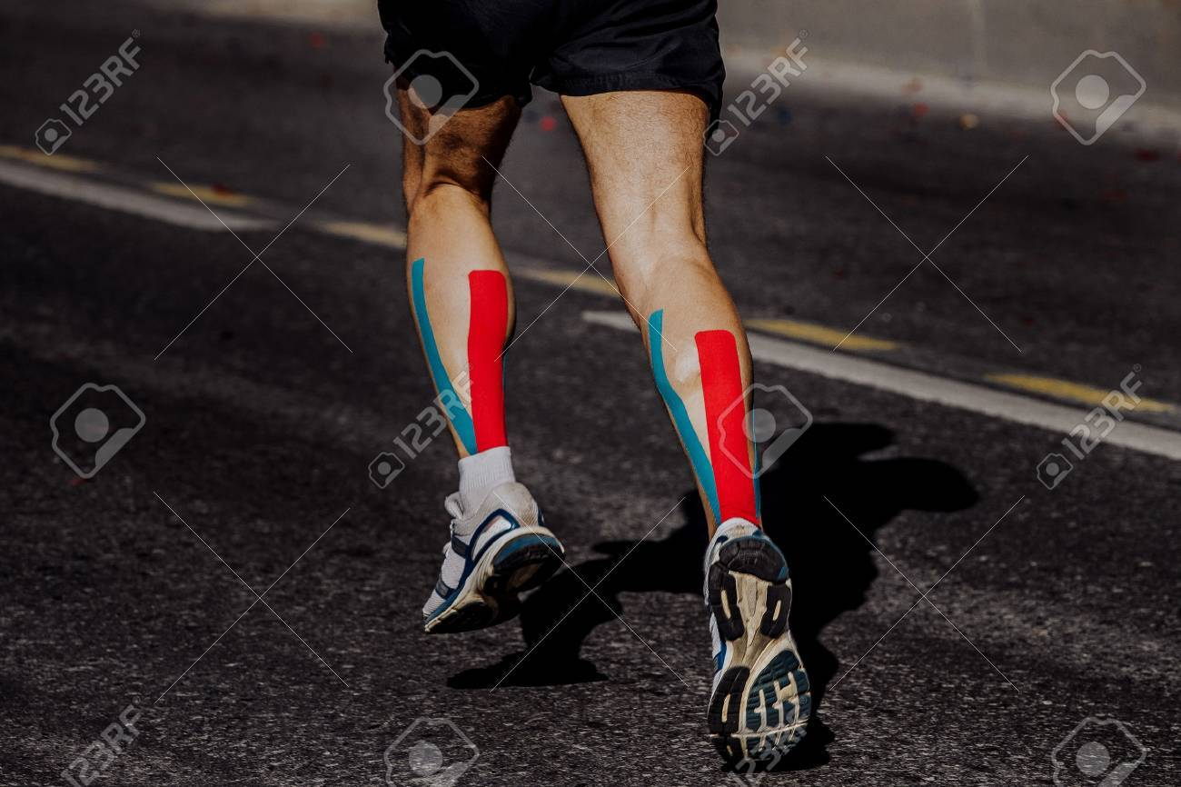 kinesio taping on muscles of calf male athlete running marathon - 61632005
