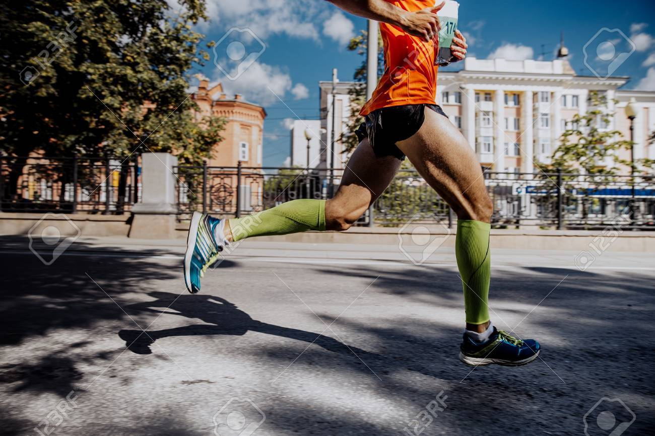 legs of a young male athlete in compression socks running marathon - 61632007