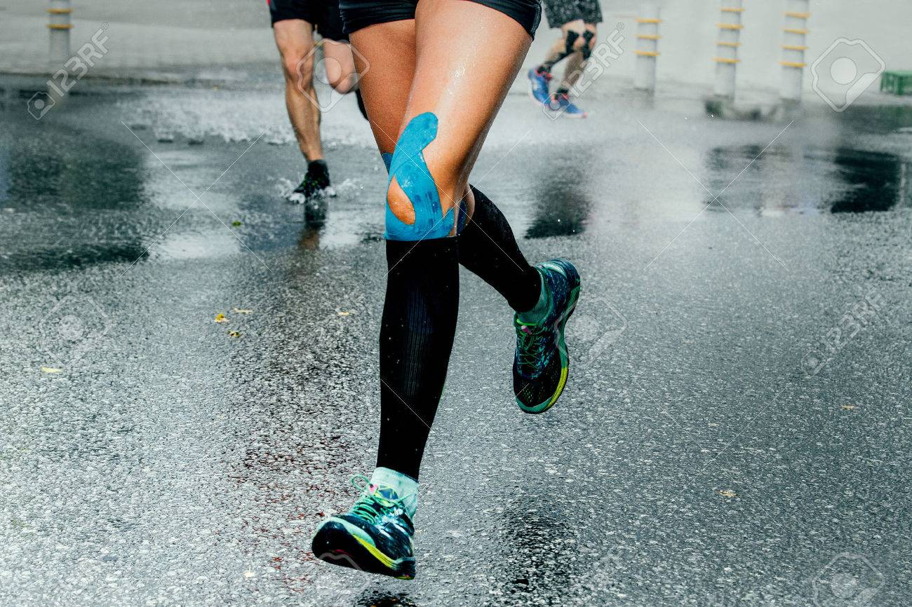 feet girl runners in compression socks and taping on his knees, running on wet asphalt - 61632028